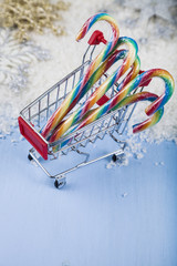 Shopping cart with Christmas candy in the snow. Concept of Chris