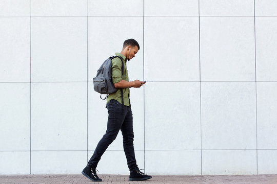 smiling man walking with backpack smart phone and headphones