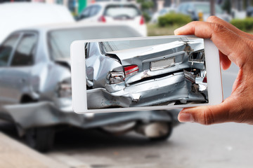Close up hand holding smartphone and take photo of car accident