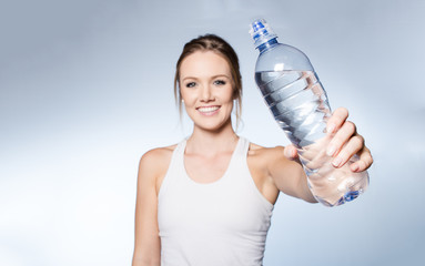 Female fitness model with water bottle on white background.