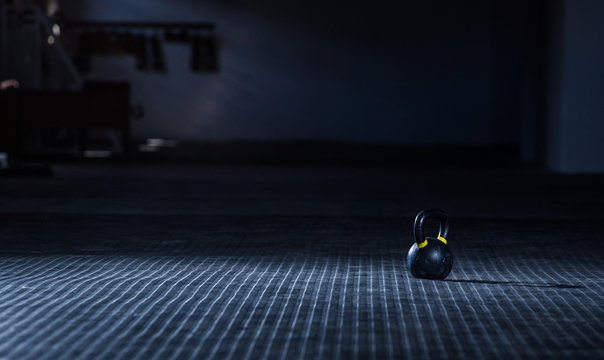 Kettle bell weight in a dark gym with moody and edgy lighting
