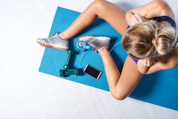 Female fitness model resting after a workout and taking selfie