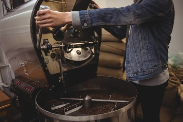 Man using grinding machine in coffee shop