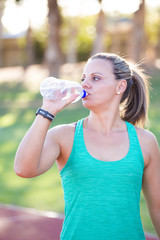 Fit Female fitness model drinking water right before she starts training