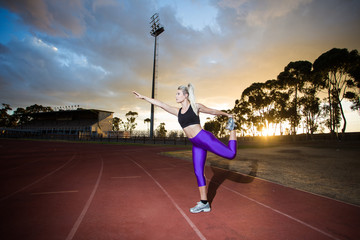Beautiful female fitness model stretching and training on athlet