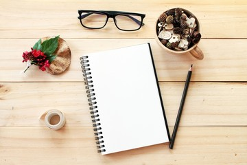 Business, work day, Christmas or New Year concept : Workspace desk with notebook, pencil, pine cones in tea wooden cup, eye glasses, christmas decoration and ribbon on wooden background