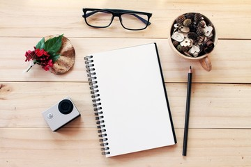 Business, work day, christmas or new year concept : Workspace desk with notebook, pencil, pine cones in tea wooden cup, eye glasses, red flower and small action camera on wooden background
