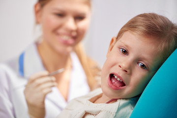 Scared kid with open mouth sitting on chair in dentist office. Teeth filling and treatment concept.