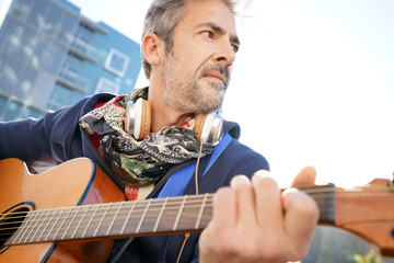 Mature trendy guy playing the guitar in the street