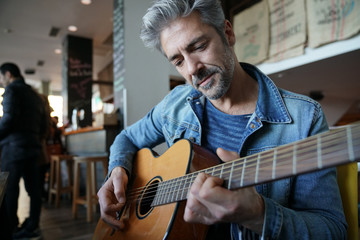 Mature trendy guy playing the guitar in a bar