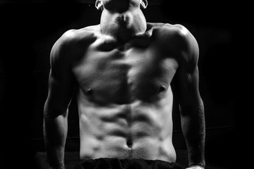 Male fitness model showing muscles in studio with a black backgr