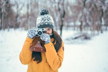Stylish woman photographer with retro camera