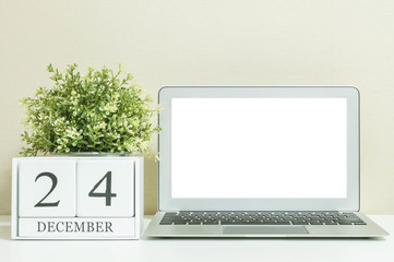 White wooden calendar with black 24 december word with white blank space at center of computer notebook on white wood desk and cream wallpaper textured background , selective focus at the calendar