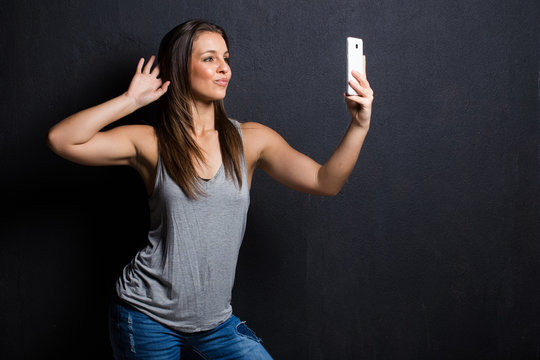 Pretty Brunette model using a smart phone to listen to music or take a selfie to load onto social meida