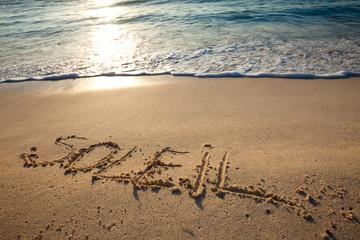 mot soleil écrit en français sur le sable sur la plage