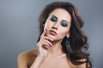 Fashion beauty portrait of a beautiful young brunette woman with make-up peacock colors on a gray background.