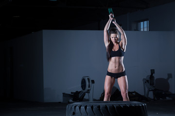 Female fitness model hitting a tractor tyre with hammer.