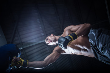 Male Athlete boxer punching a punching bag in a gym