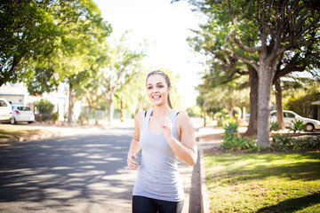 Female fitness model running and jumping in a street in a suburban area while training