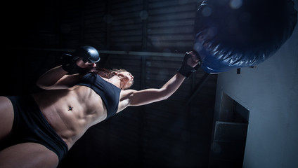 Female Athlete boxer punching a punching bag in a gym