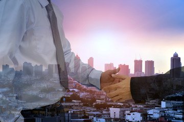 Businessman hand shake for business , stock  chart and city background .