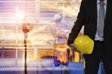 Construction safety concept , engineer  holding yellow helmet and blur construction background .
