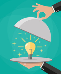 Hands holding platter cloche with idea light bulb
