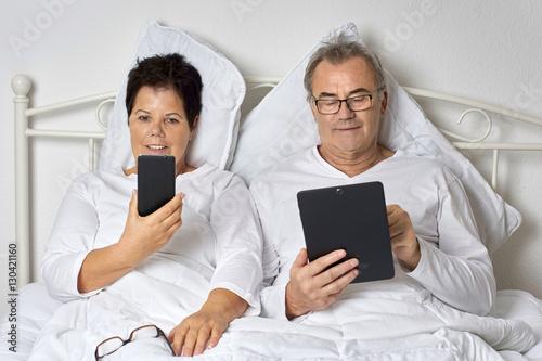 senioren mit handy und tablet im schlafzimmer im bett. Black Bedroom Furniture Sets. Home Design Ideas