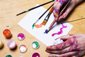 Hands of the artist  in bright colored paint with brush on wooden table. Woman draws on a sheet of paper