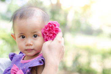 Asian baby girl with pink rose flower in her hair on light natur