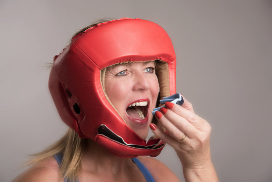 Female boxer wearing a safety head guard and inserting a gum shield into her mouth