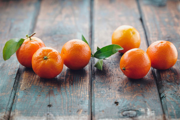 Fresh clementines with leaves on wooden table.