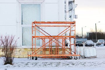 small orange building mobile work scaffolding near a large sports complex.