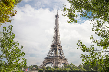 View on Eiffel tower through green trees with cloud bckground. Eiffel Tower from Champ de Mars, Paris, France.