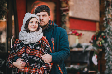Happy couple in warm clothes posing on a Christmas market. Holiday mood