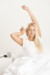 Beautiful  blonde woman has woken up and is sitting on a white bed