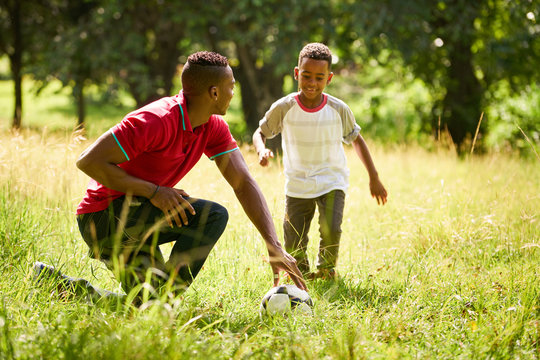 Sport Practice With Father Teaching Son How To Play Soccer