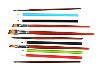 brushes painting and color pencils isolated on white