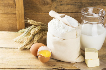 Ingredients for pastries - flour, eggs, butter, milk on a wooden
