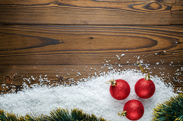 Christmas Background Theme. Red Christmas Balls On The Snow (Large Sea Salt) On A Wooden Background. Close-Up. Top View.