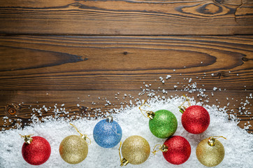 Christmas Background Theme. Multicolored Christmas Balls (Red, Blue, Green, Silver, Gold) In The Snow (Large Sea Salt) On A Wooden Background. Close-Up. Top View.