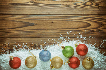 Christmas Background Theme. Multicolored Christmas Balls (Red, Blue, Green, Gold) In The Snow (Large Sea Salt) On A Wooden Background. Close-Up. Top View.