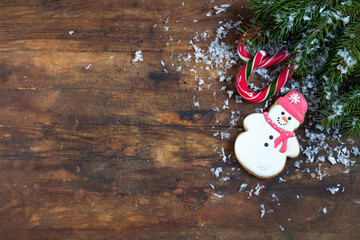 Christmas and New Year composition. Gingerbread snowman, fir tree branches and candy cane with snow on dark wooden background.