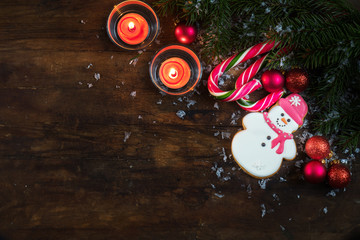 Christmas and New Year composition. Gingerbread snowman, fir tree branches, balls, light two candles and candy cane with snow on dark wooden background.