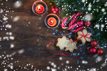 Christmas and New Year composition. Christmas cookies with festive decoration, fir tree branches, balls, light two candles,  candy cane and snow on dark wooden background.