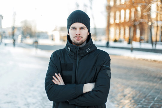 Handsome young man in a knitted cap and a black jacket on a winter day