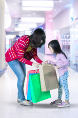 Young woman and child looking shopping bag