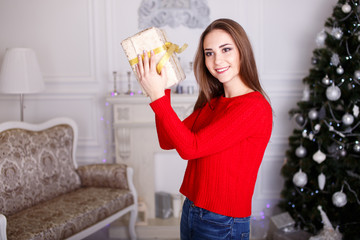 Smiling young woman with a Christmas gifts and Christmas tree.