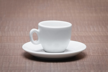 Clean and empty ceramic cup for espresso with saucer on wooden t