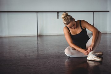 Young woman adjusting ballet shoe